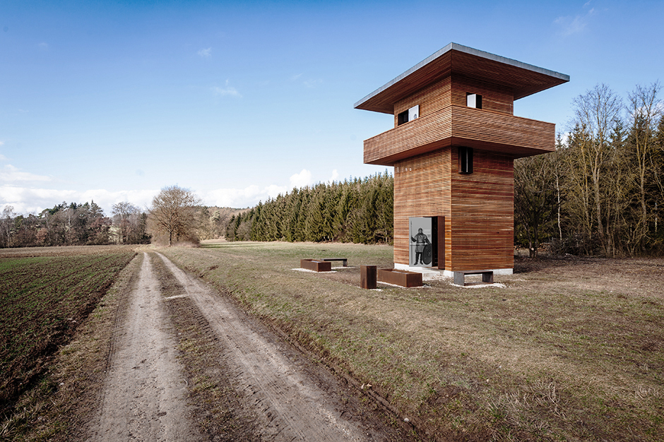 Ausstellungsarchitektur. Aussichtsturm auf einem Feld vor einem Wald.