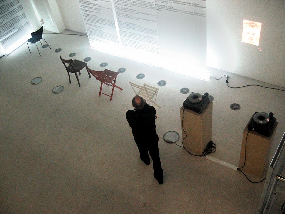 Wanderausstellung. Mann vor Ausstellungswand und Stühlen.