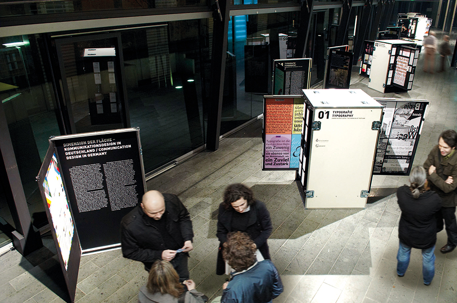 Ausstellungsarchitektur. Personen vor mobilen Vitrinen in Form von Industrie Containern.