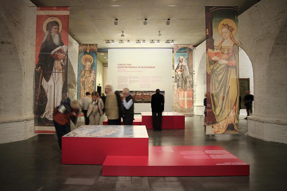 Museumsdesign. Besucher vor Vitrinen mit Bild und Text, christliche Figuren.