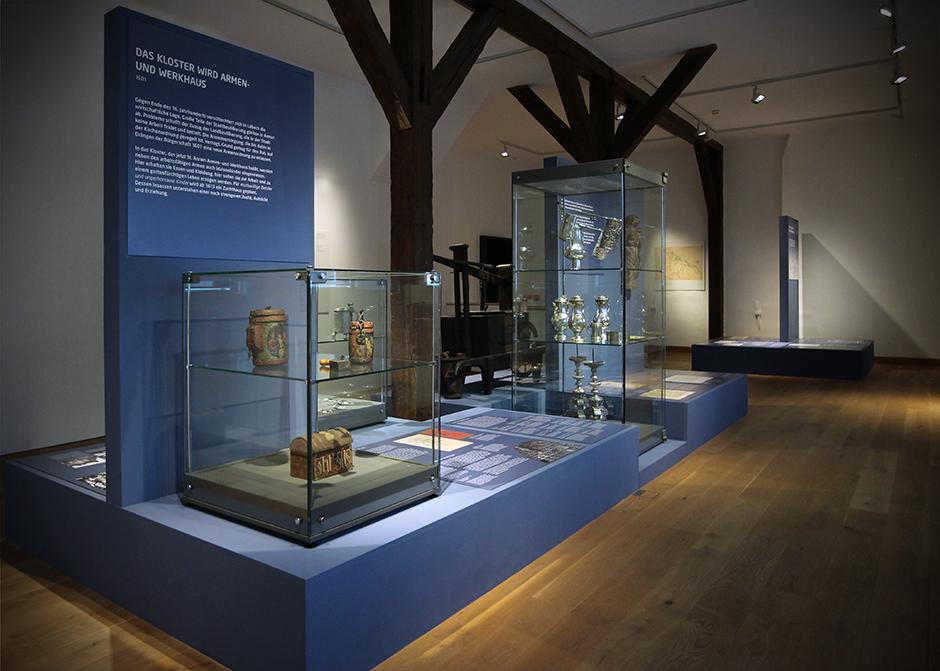 Museumsgestaltung. Glasvitrine, auf dunkelblauem Sockel, mit verschiedenen Grafiken.