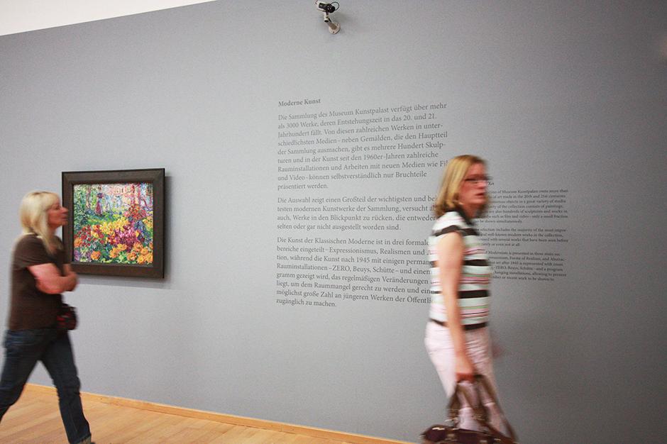 Museumsgestaltung. Besucherinnen betrachten einen Ausstellungsraum mit einer Grafik an der Wand.
