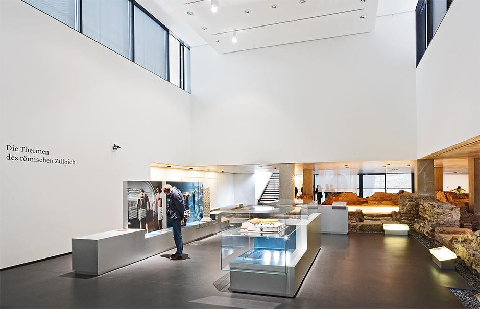 Museumsplanung. Mann vor Glasvitrinen, Ausstellungsarchitektur.
