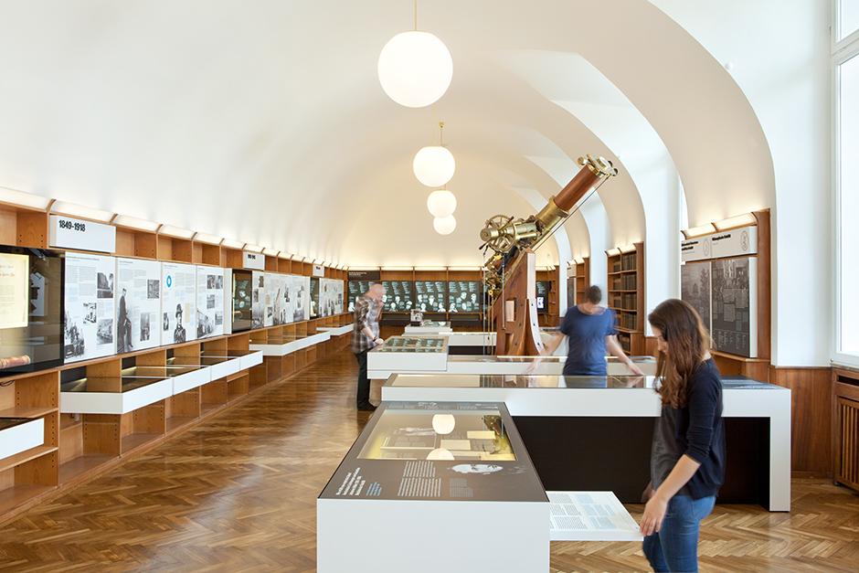 Ausstellungsdesign. Besucher vor Vitrinen-Tischen und Vitrinen an der Wand.
