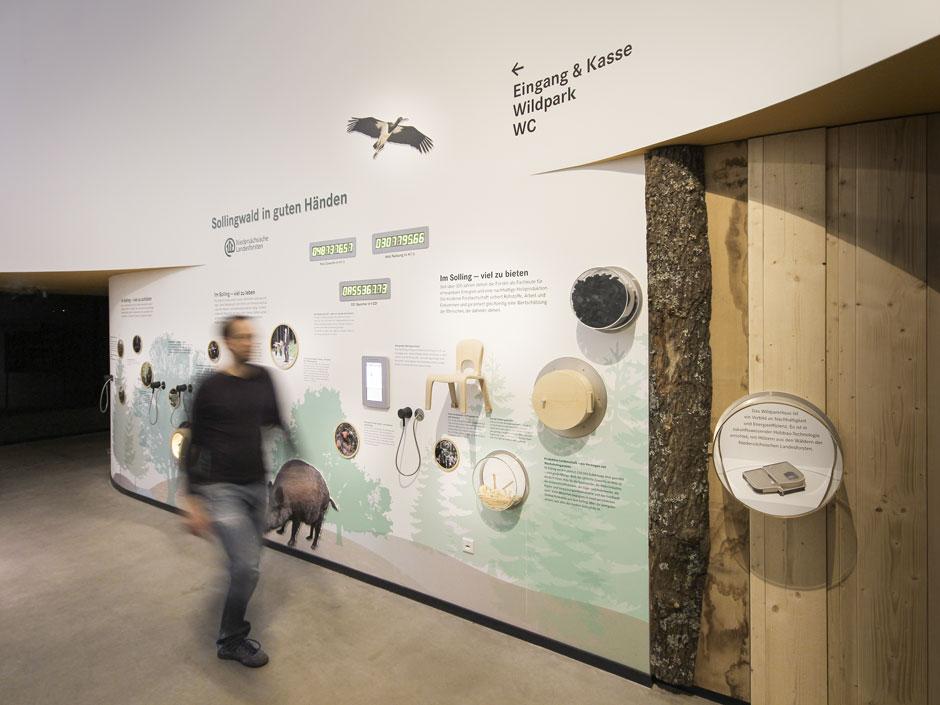 Museumsgestaltung. Besucher vor Ausstellungswand.