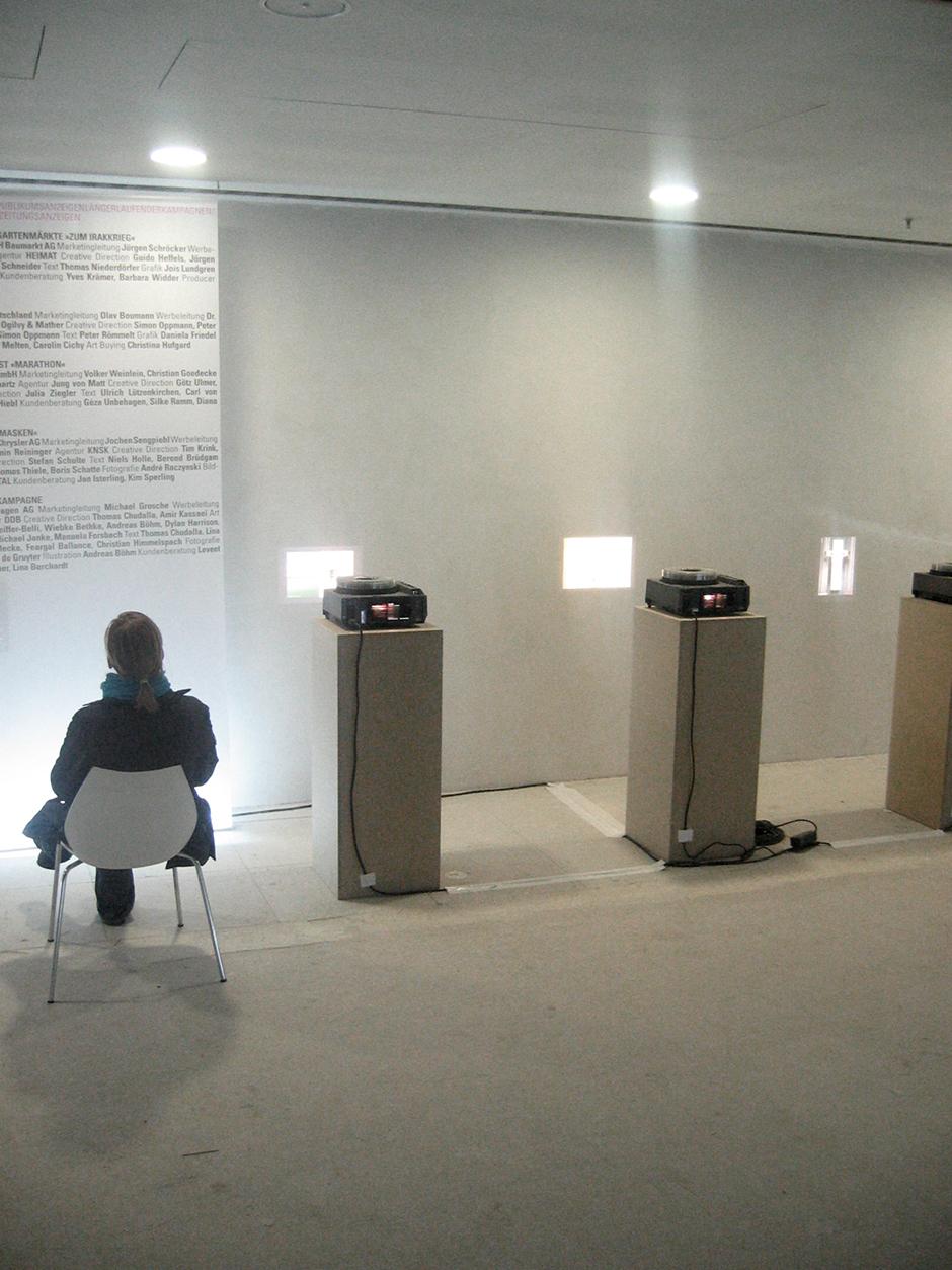 Wanderausstellung. Frau auf einem Stuhl vor Ausstellungswand.