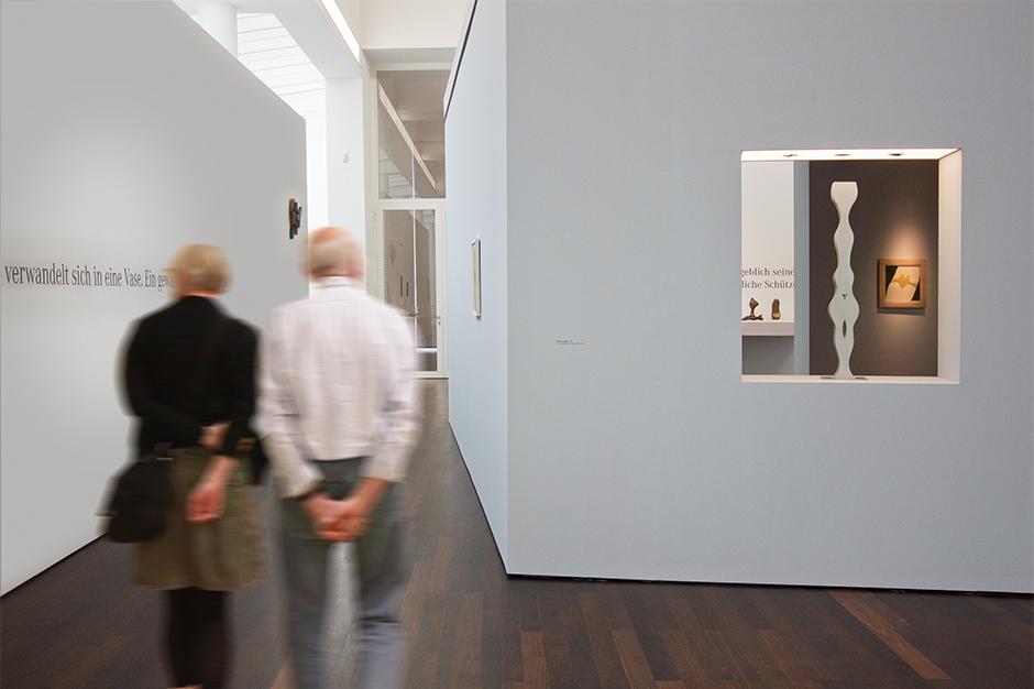 Ausstellungsgestaltung. Personen vor offener Vitrine in einer Wand.
