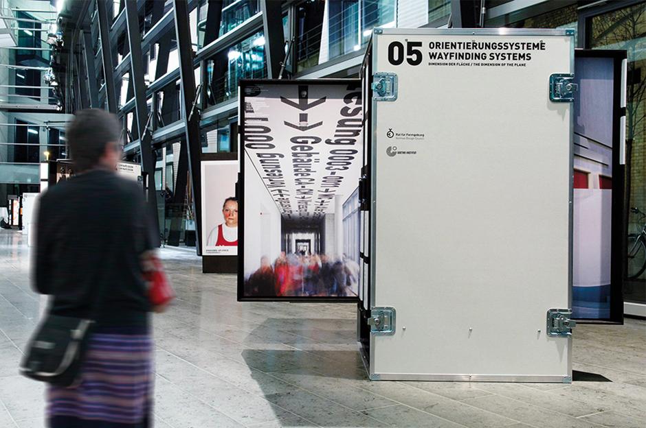 Ausstellungsarchitektur. Frau vor mobilen Vitrinen in Form von Industrie Containern.