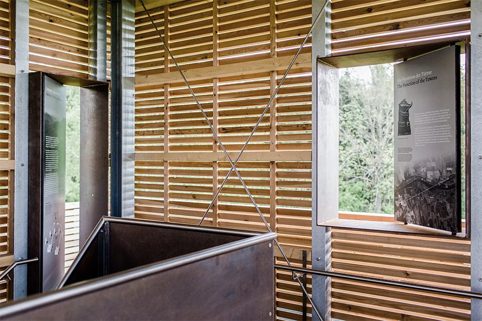 Ausstellungsarchitektur. Aussicht in den Wald durch Holz-Fugen, Grafik im Fenster.