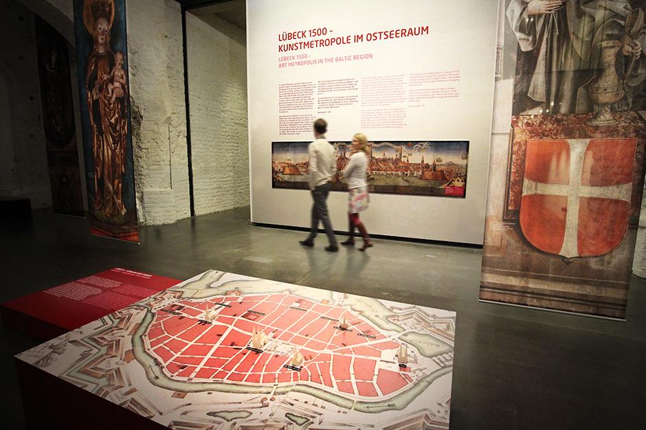 Museumsdesign. Besucher vor Ausstellungswand mit Bild und Text.