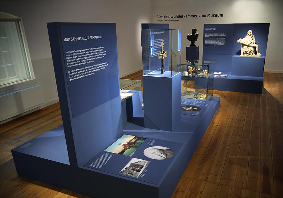 Museumsgestaltung. Glasvitrinen, auf dunkelblauen Sockeln, mit verschiedenen Grafiken.