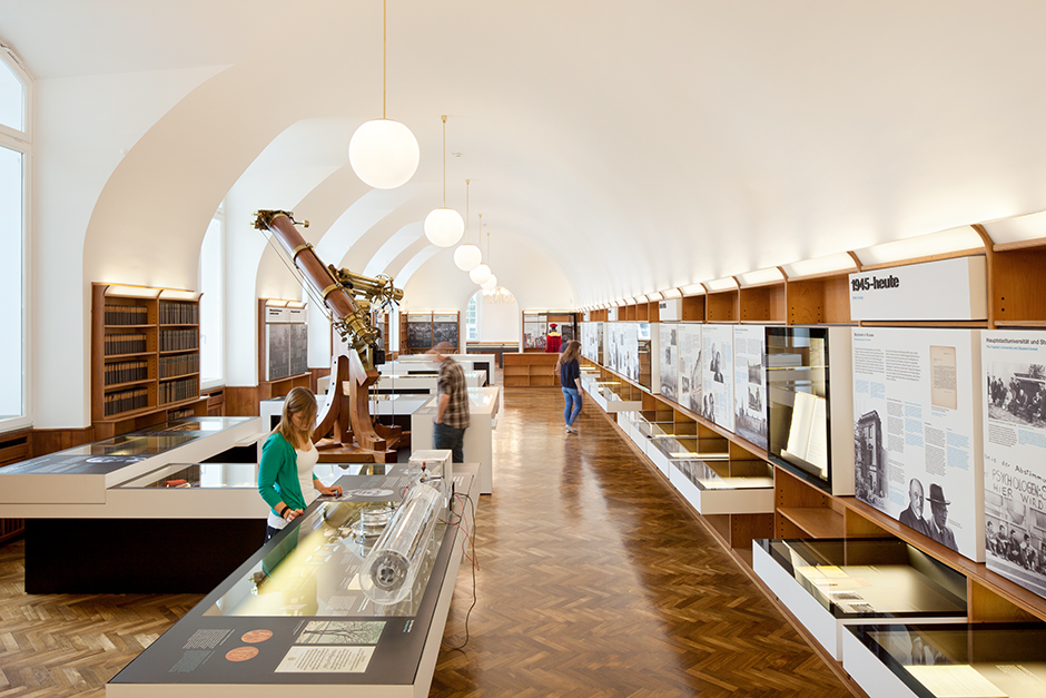 Ausstellungsdesign. Besucher vor Vitrinen-Tischen und Vitrinen in der Wand.