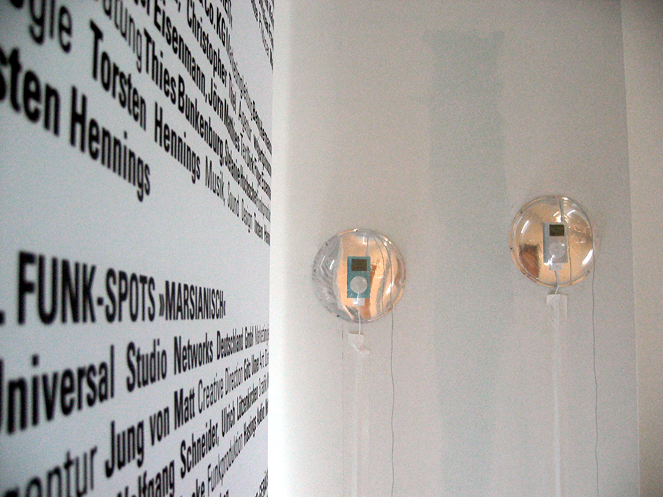 Ausstellungsdesign. Detailaufnahme. Grafik an der Wand und iPods in gesicherter Kugel für audiovisuelle Medien.