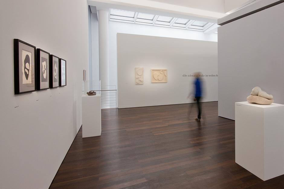 Ausstellungsgestaltung. Person betrachtet ausgestelltes an einer Wand.