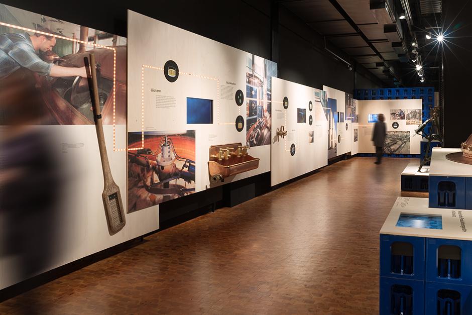 Museumsdesign. Ausstellungssituation mit Bierkästen und Grafiken an der Wand.