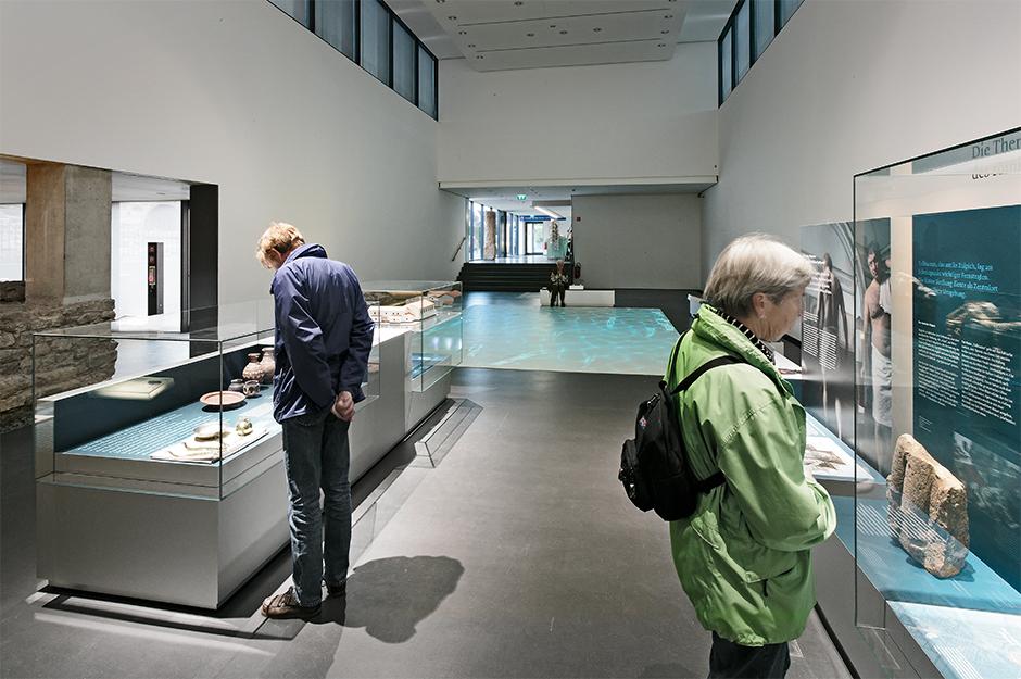 Museumsplanung. Besucher vor Glasvitrinen.