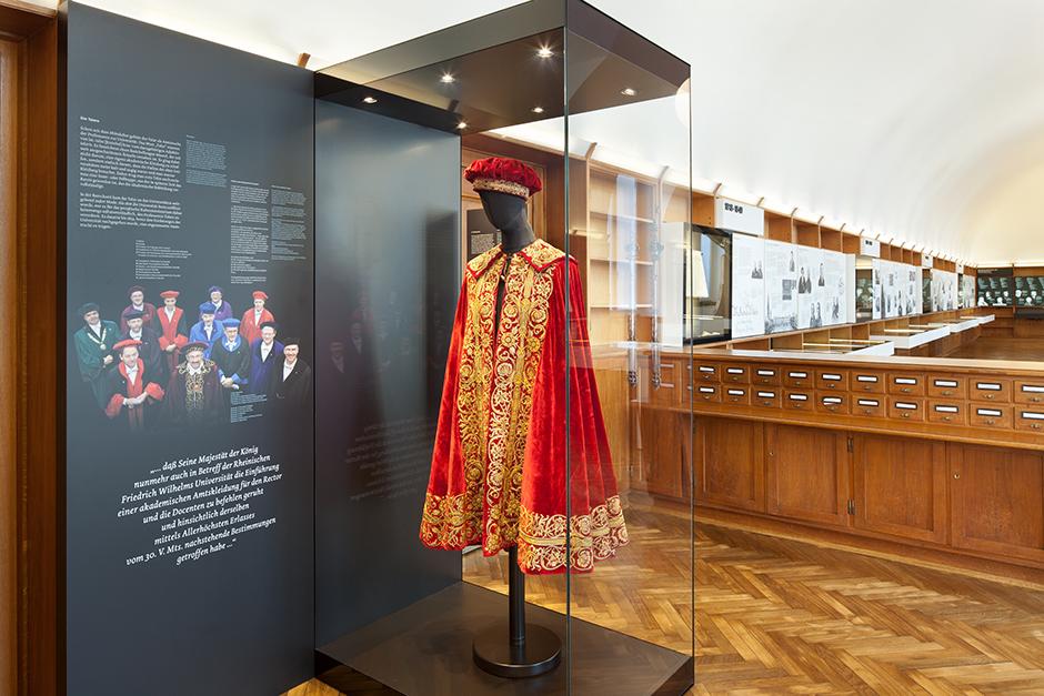 Ausstellungsdesign. Vitrine mit rot/goldenem Mantel.