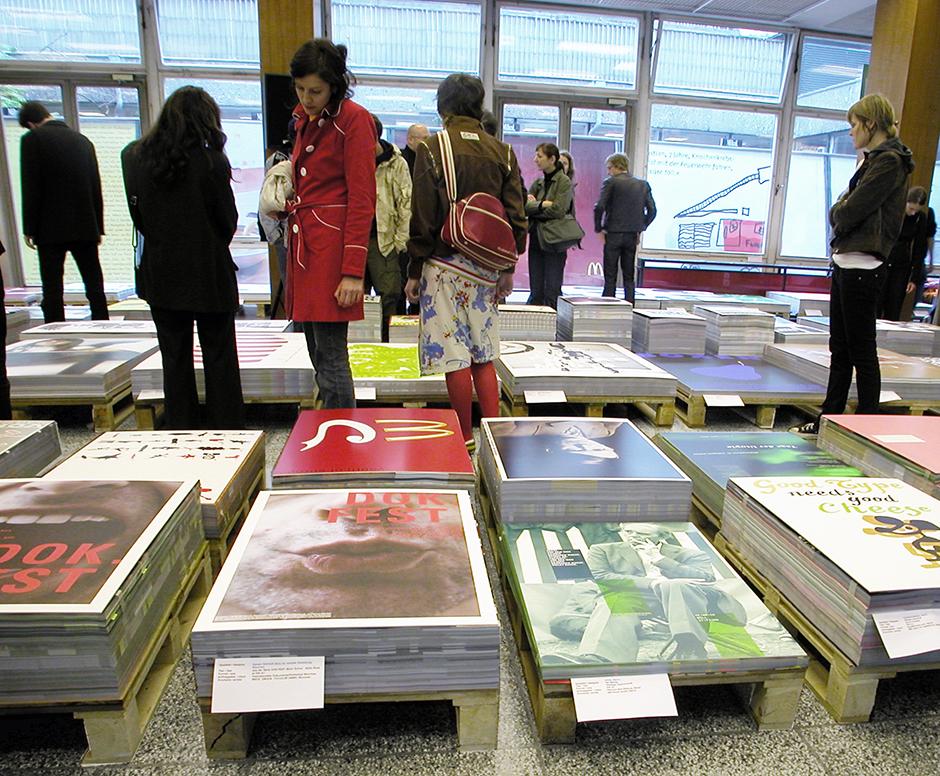 Ausstellungsdesign. Plakate auf Paletten, umgeben von Besuchern.