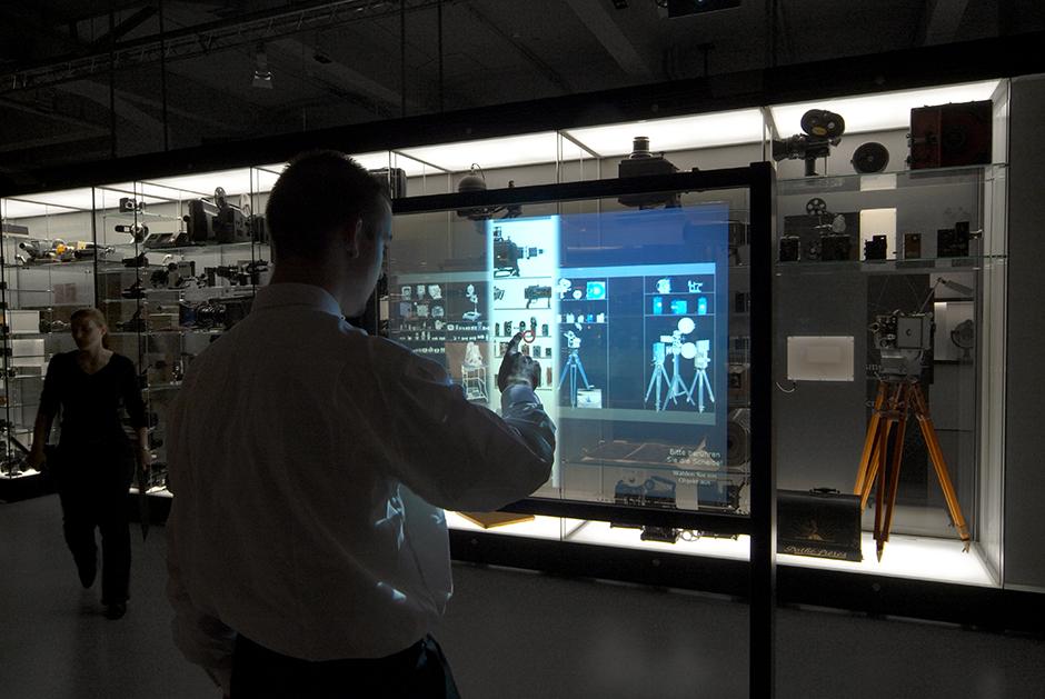 Ausstellungsplanung. Person vor interaktivem Bildschirm.