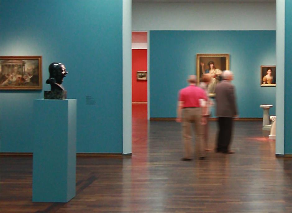 Museumsgestaltung. Besucher in einem Ausstellungsraum.