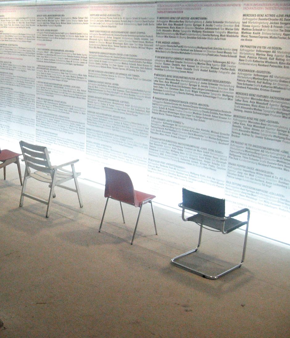 Wanderausstellung. Sitzgelegenheiten vor den Grafiken an der Wand.