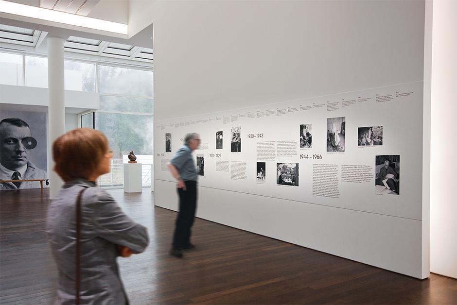 Ausstellungsgestaltung. Personen betrachten Grafik an der Wand.