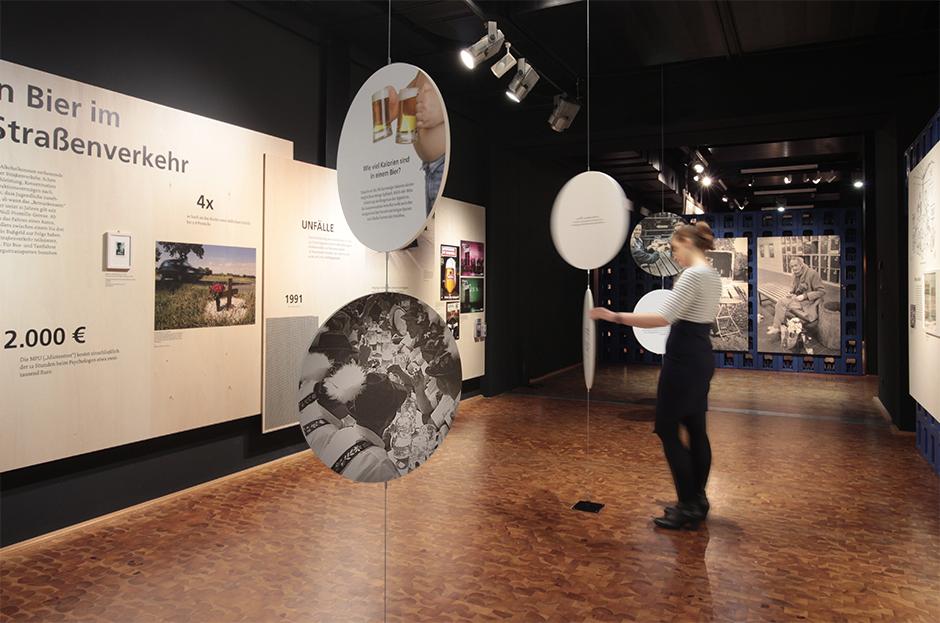 Museumsdesign. Ausstellungssituation mit Besucherinn in der Mitte des Raumes.