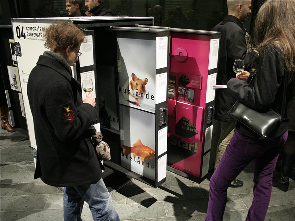 Ausstellungsarchitektur. Personen um eine mobile Vitrine.