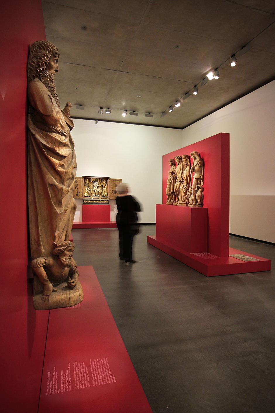 Museumsdesign. Besucher vor Ausstellungswand alten Holzfiguren, Holzfigur im Vordergrund.