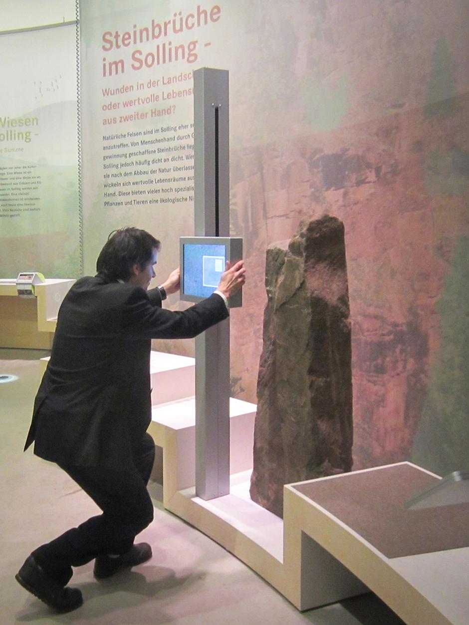 Museumsgestaltung. Besucher vor interaktivem Teil der Ausstellung.