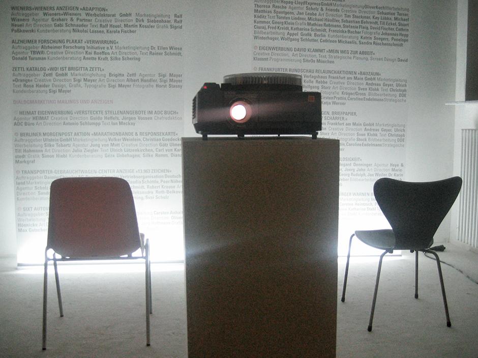 Wanderausstellung. Projektor im Vordergrund, Grafiken an der Wand im Hintergrund.