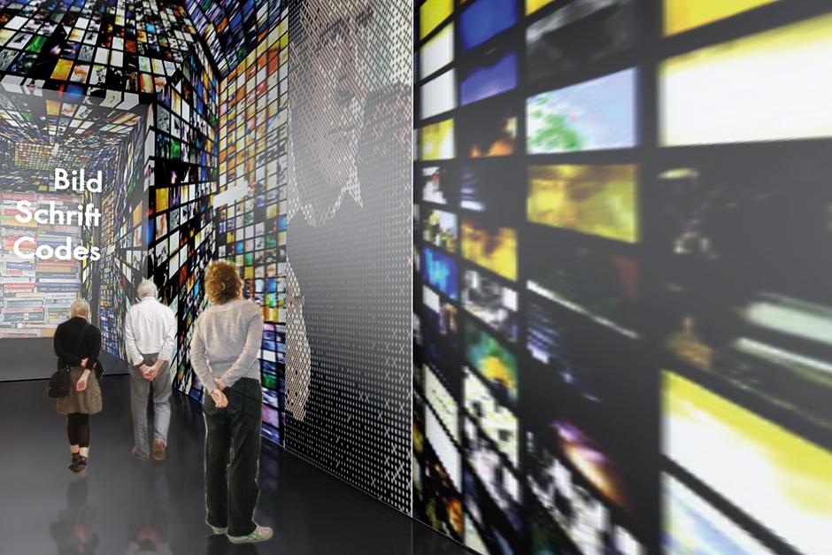 Ausstellungsarchitektur. Personen vor Grafiken an der Wand.