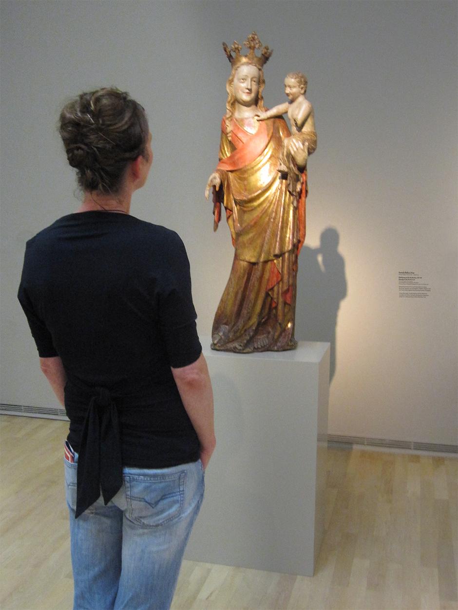 Museumsgestaltung. Besucherin betrachtet eine Figur auf einem Sockel.