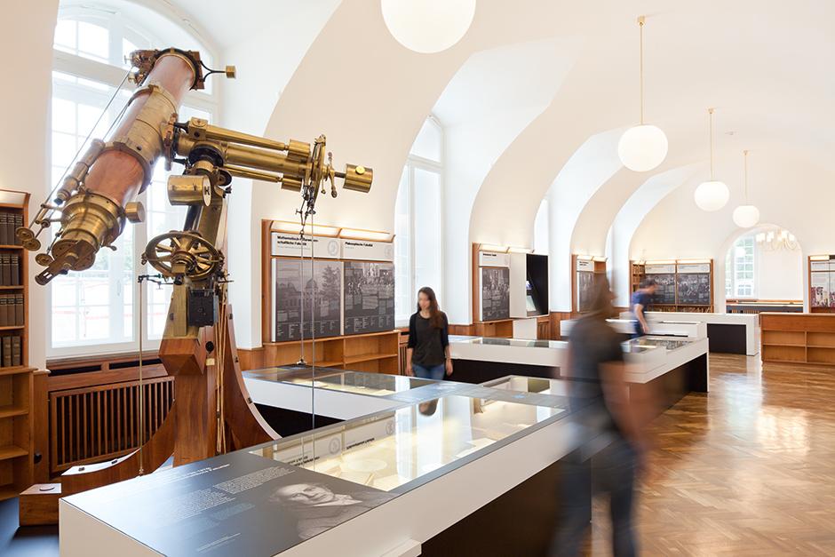 Ausstellungsdesign. Besucher vor Vitrinen-Tischen, großes Teleskop.