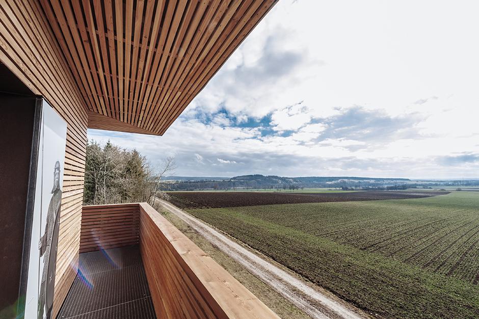 Ausstellungsarchitektur. Aussicht vom Turm über Felder, blauer Himmel.