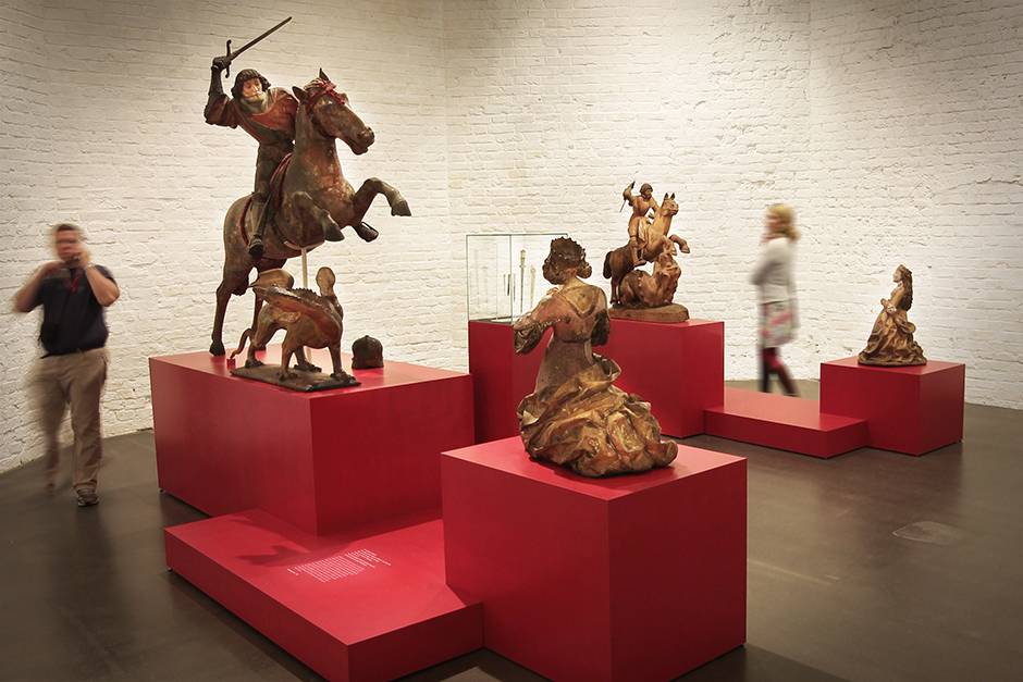 Museumsdesign. Sockel, rot, mit unterschiedlichen Figuren.