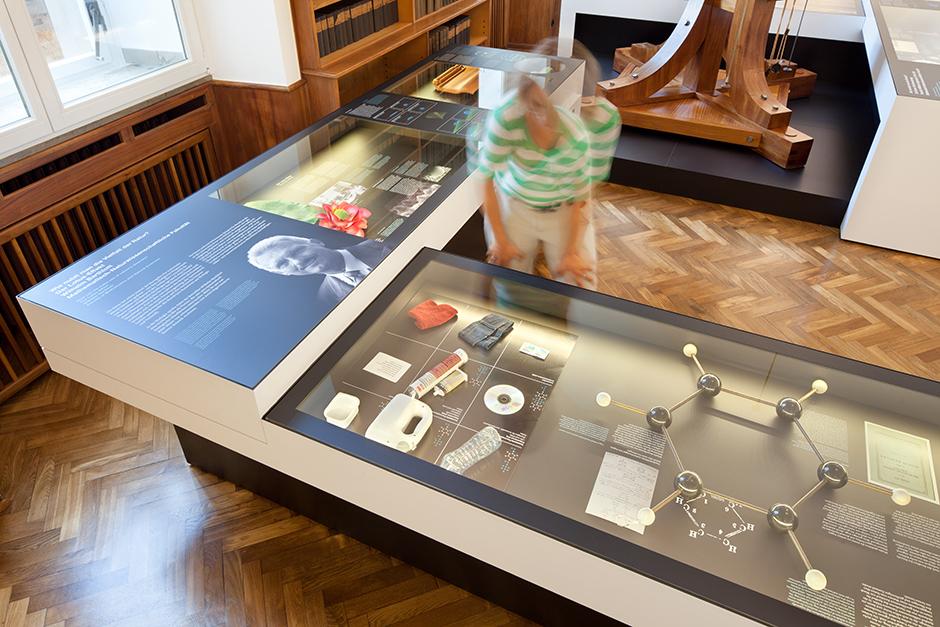 Ausstellungsdesign. Besucherin vor einem Vitrinen-Tisch.