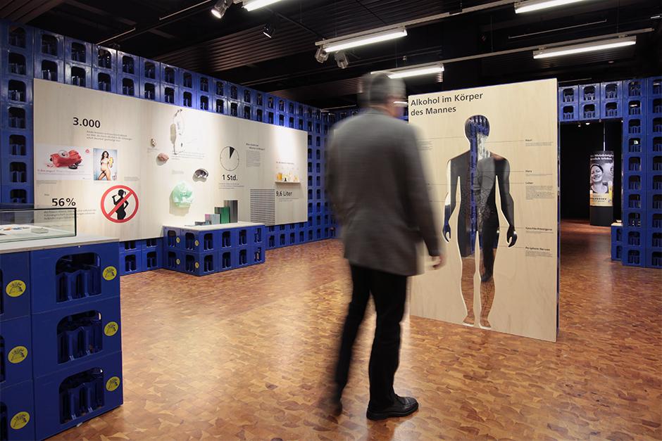 Museumsdesign. Besucher vor Grafik, Wände aus Bierkästen.