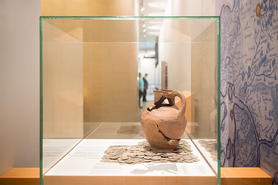 Ausstellungsdesign. Vitrine mit zerbrochener Vase und alten Geldmünzen.