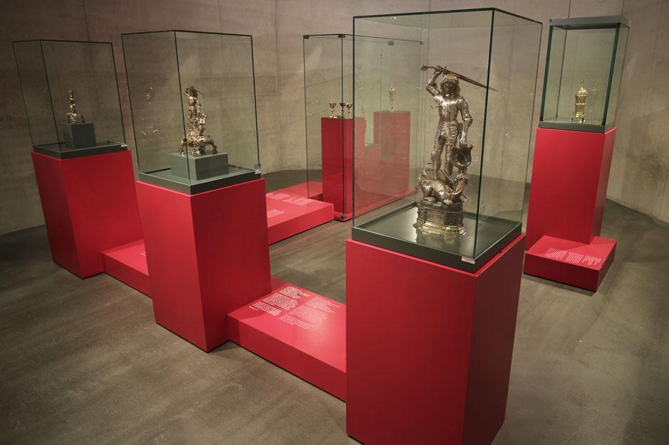 Museumsdesign. Vitrinen, rot, mit verschieden, silbernen Figuren.