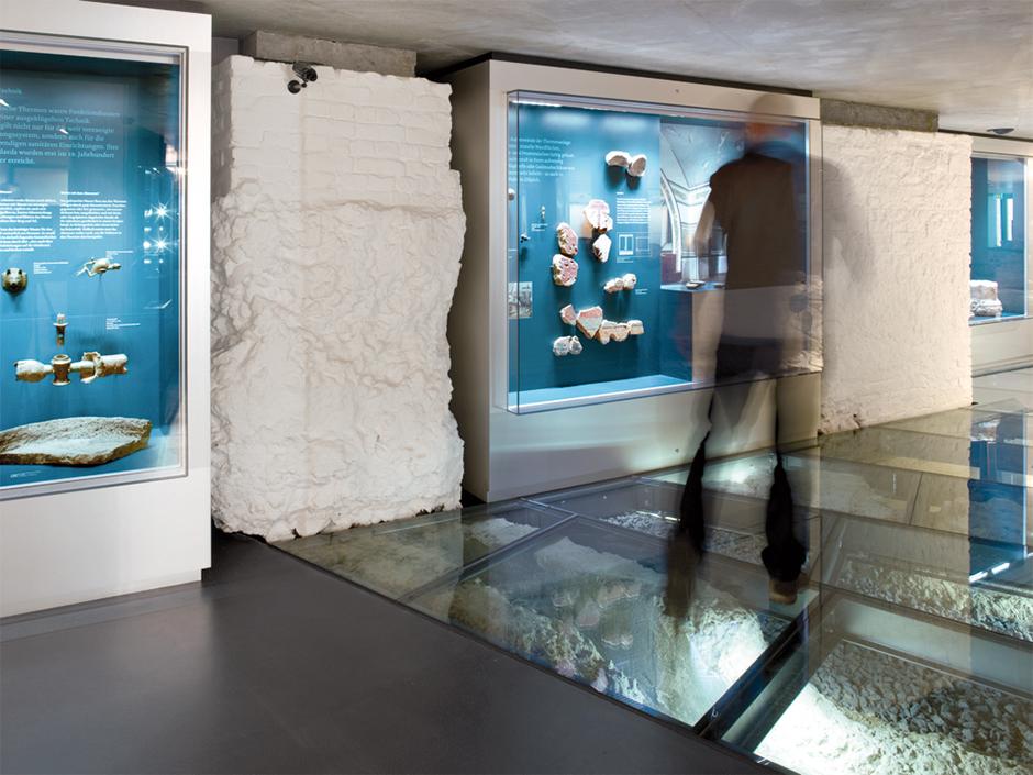 Museumsplanung. Mann in Bewegung vor Glasvitrinen in der Wand.