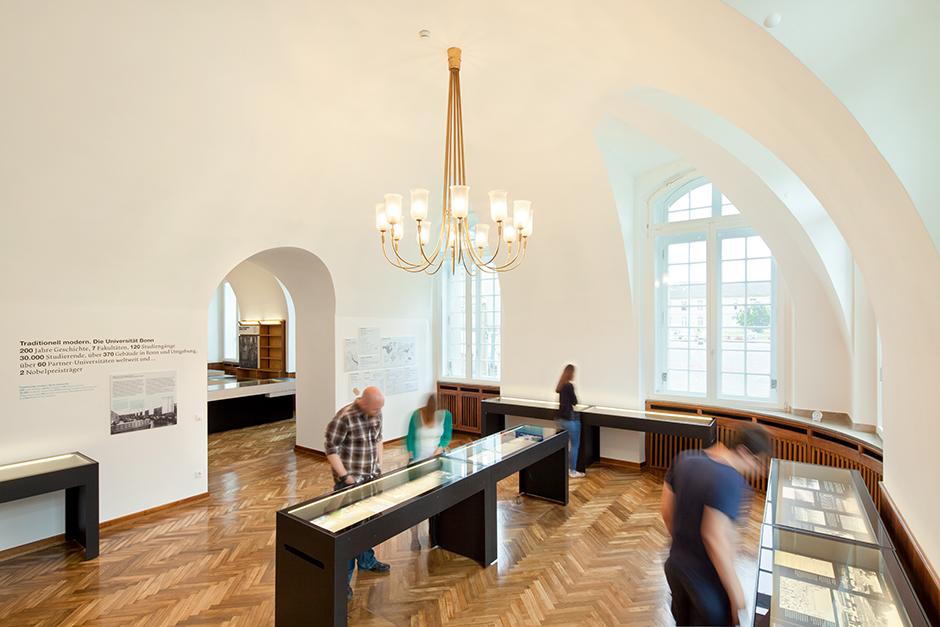 Ausstellungsdesign. Besucher vor Vitrinen-Tischen.