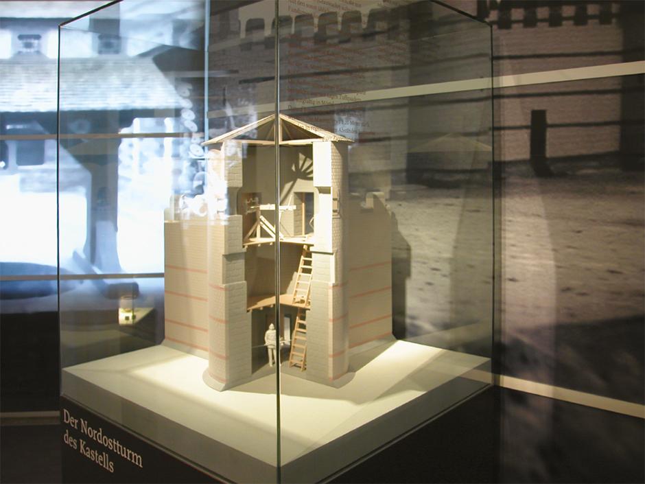 Szenographie. Modell eines Römerturms in einer Vitrine.