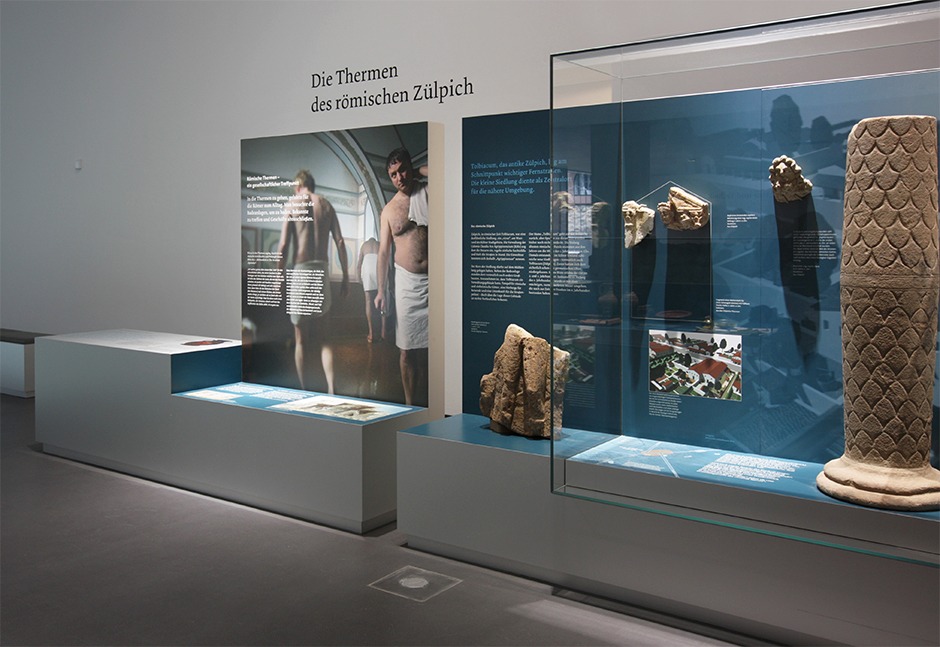 Museumsplanung. Grafiken an der Wand, Vitrinen mit Ausstellungsstücken.