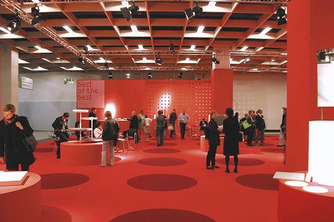 Ausstellungsarchitektur. Messestand, rot. Viele Besucher.