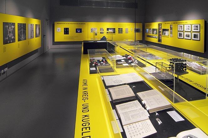 Ausstellungsarchitektur. Durchsichtige Vitrine auf gelbem Tisch.