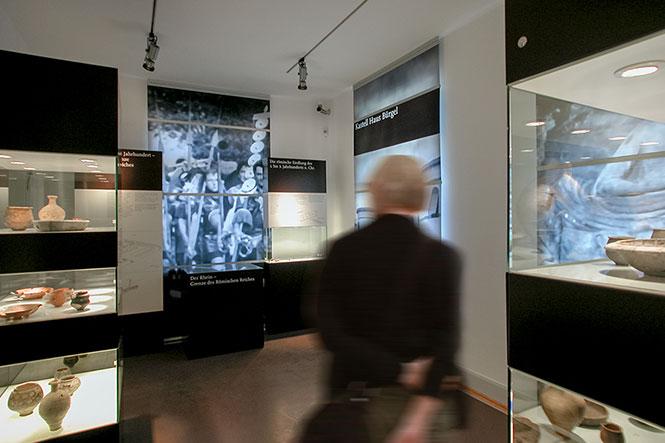 Szenographie. Mann vor Kubusen im Ausstellungsraum.