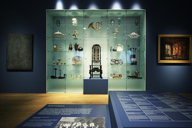 Museumsgestaltung. Glasvitrine, hellblau vor dunkelblauer Wand.