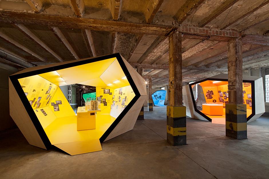 Ausstellungsarchitektur. Begehbarer Ausstellungskörper, gelb, in Fabrikhalle.