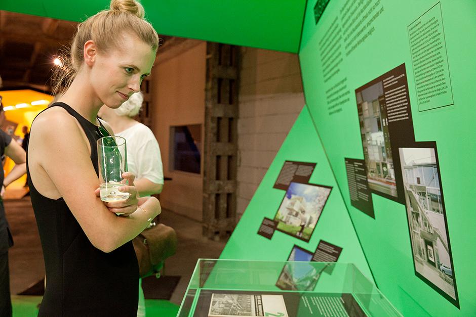 Ausstellungsarchitektur. Begehbarer Ausstellungskörper, Innen, grün. Frau steht vor Vitrine mit Text.